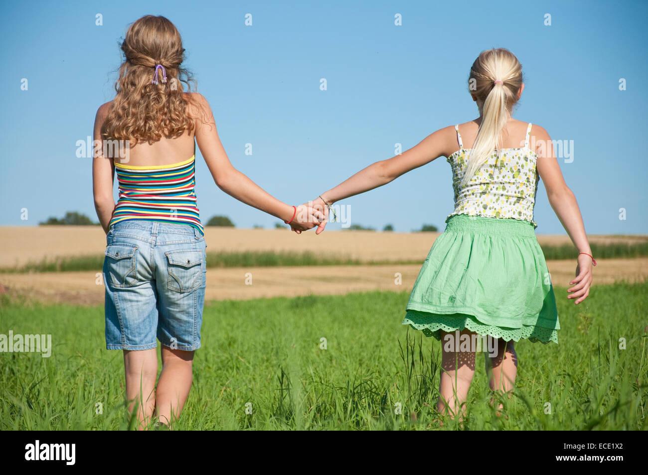 Deux jeunes filles (10-11) (12-13) la main dans la main dans le champ, vue arrière Photo Stock