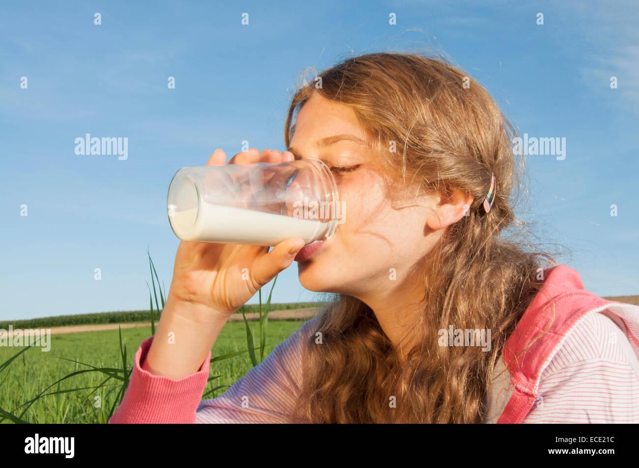 Girl (12-13), de boire dans un verre de lait à l'extérieur, les yeux clos, portrait Photo Stock