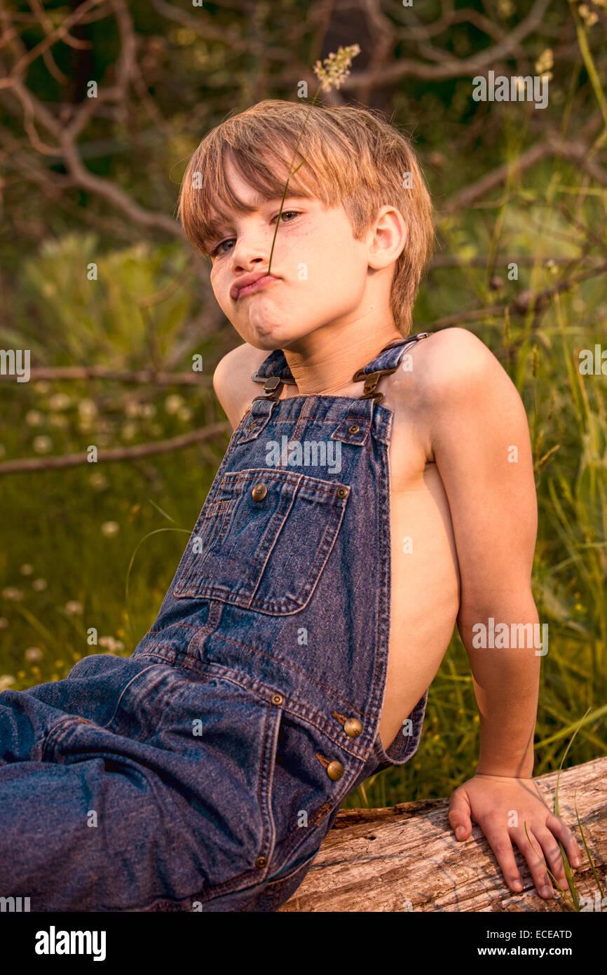 Portrait d'un garçon assis sur un tronc d'arbre pulling funny faces Photo Stock