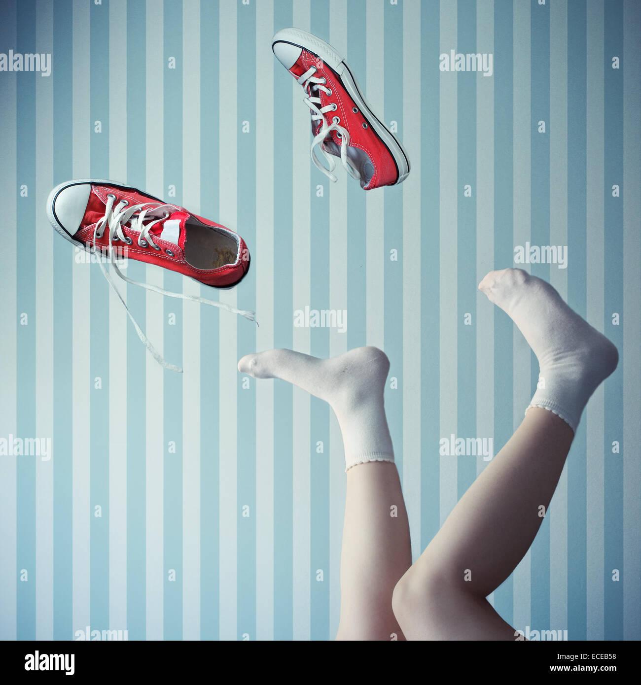Femme avec ses jambes en l'air avec des formateurs mid air Photo Stock