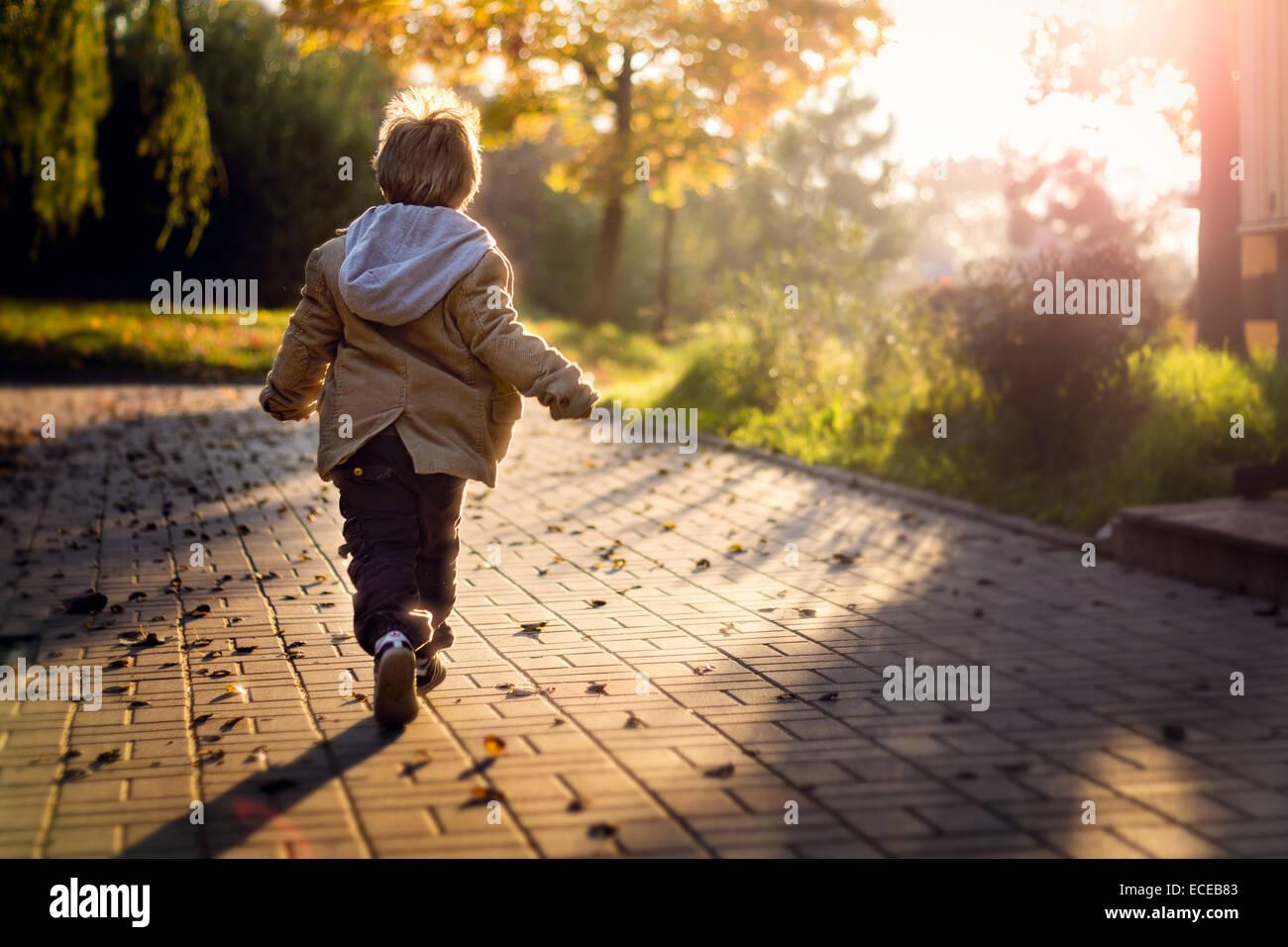 Garçon courir vers rising sun Photo Stock