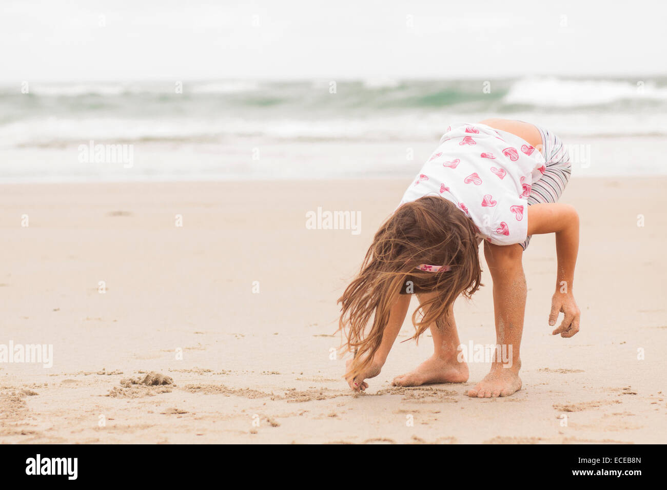 Girl (4-5) le dessin dans le sable Photo Stock