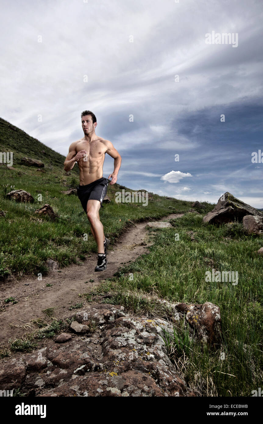USA, Californie, Comté de Jeferson, Golden, Shirtless man running long sentier coteau Photo Stock