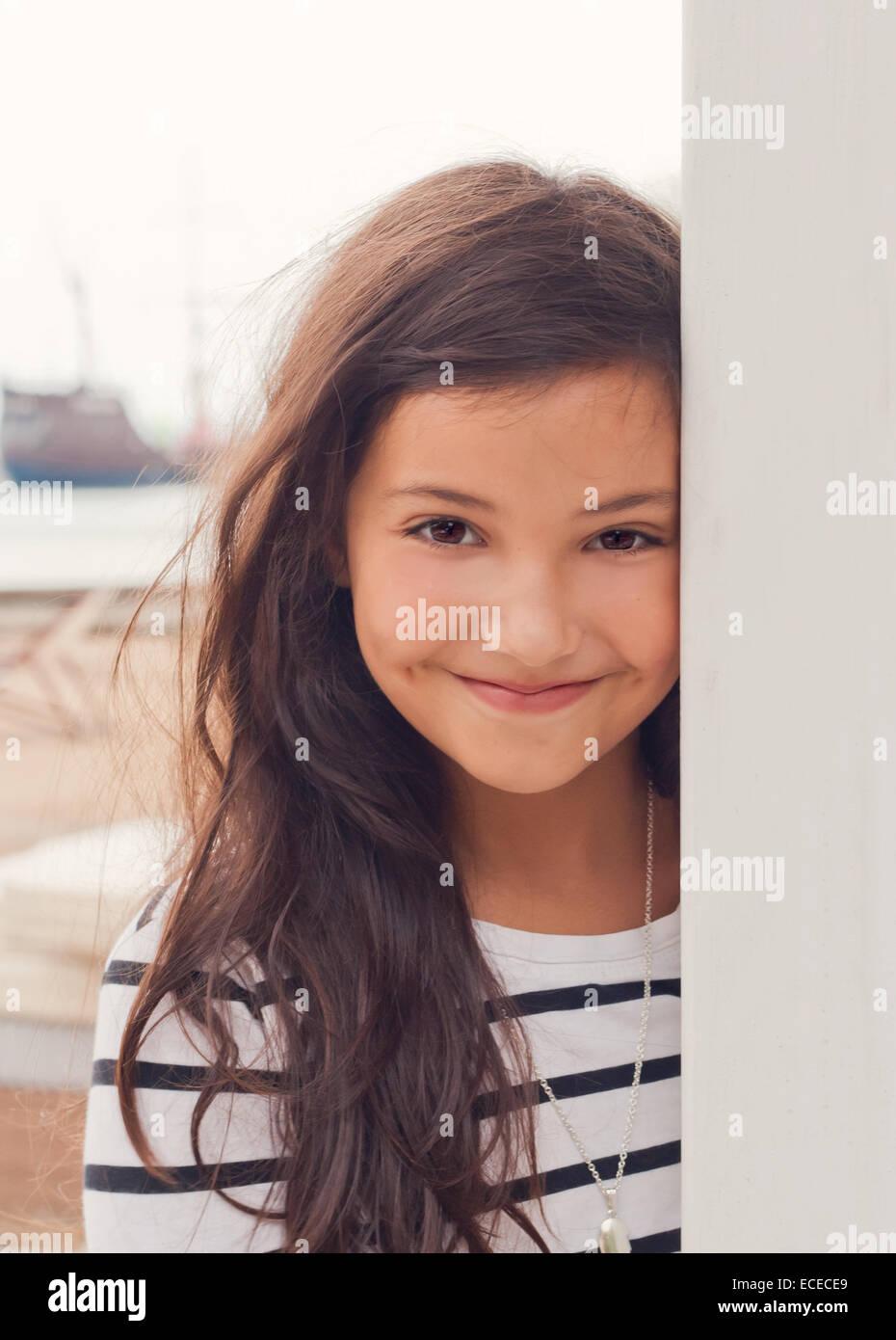 Jolie petite fille (6-7) en robe rayée smiling on beach, près de la mer Photo Stock