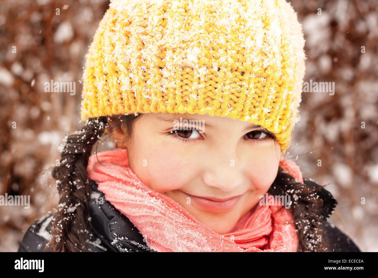 Jolie petite fille (6-7) à tresses et hat, souriant au cours de l'automne la neige Photo Stock