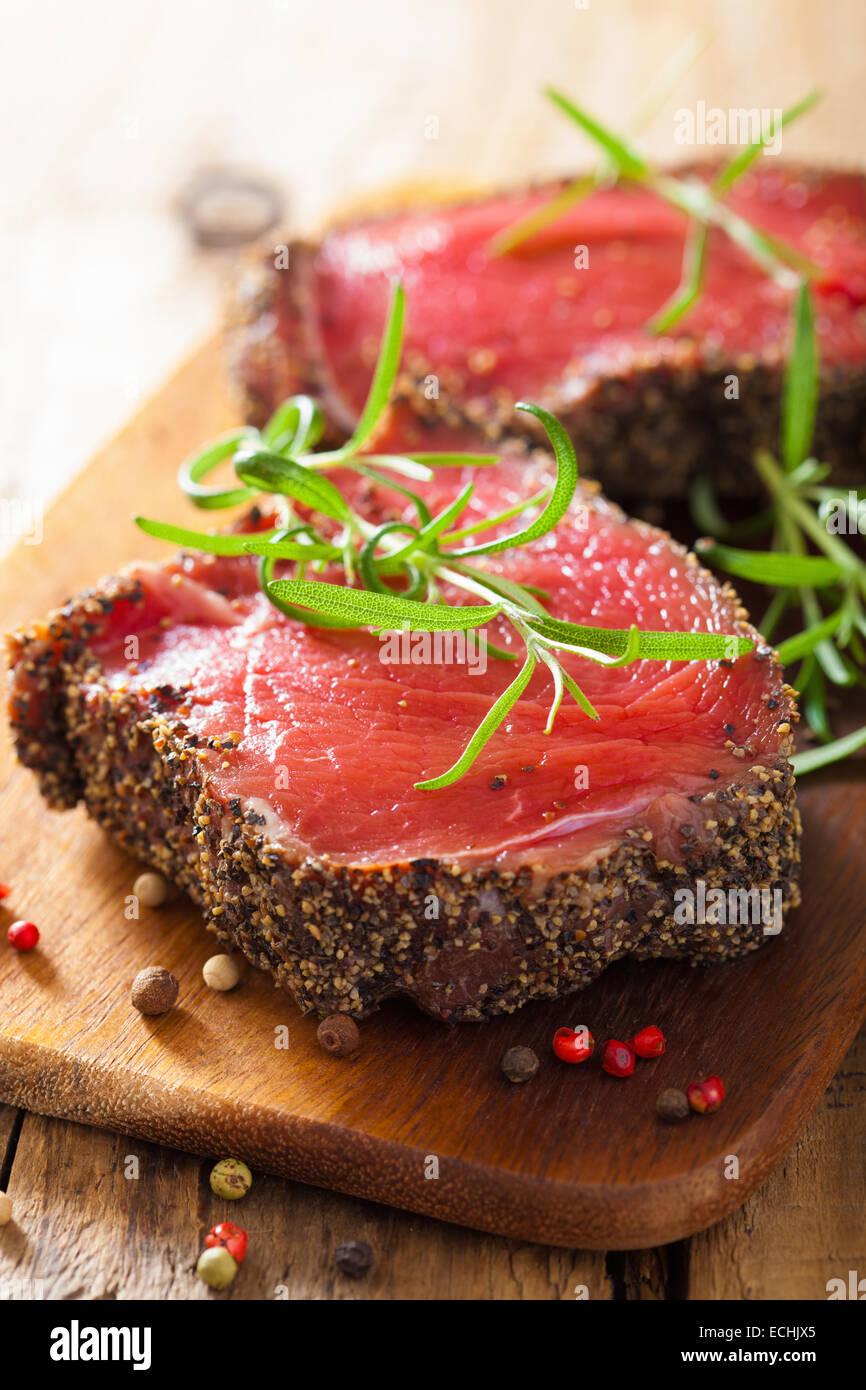 Steak de boeuf aux épices et de romarin sur fond de bois Photo Stock