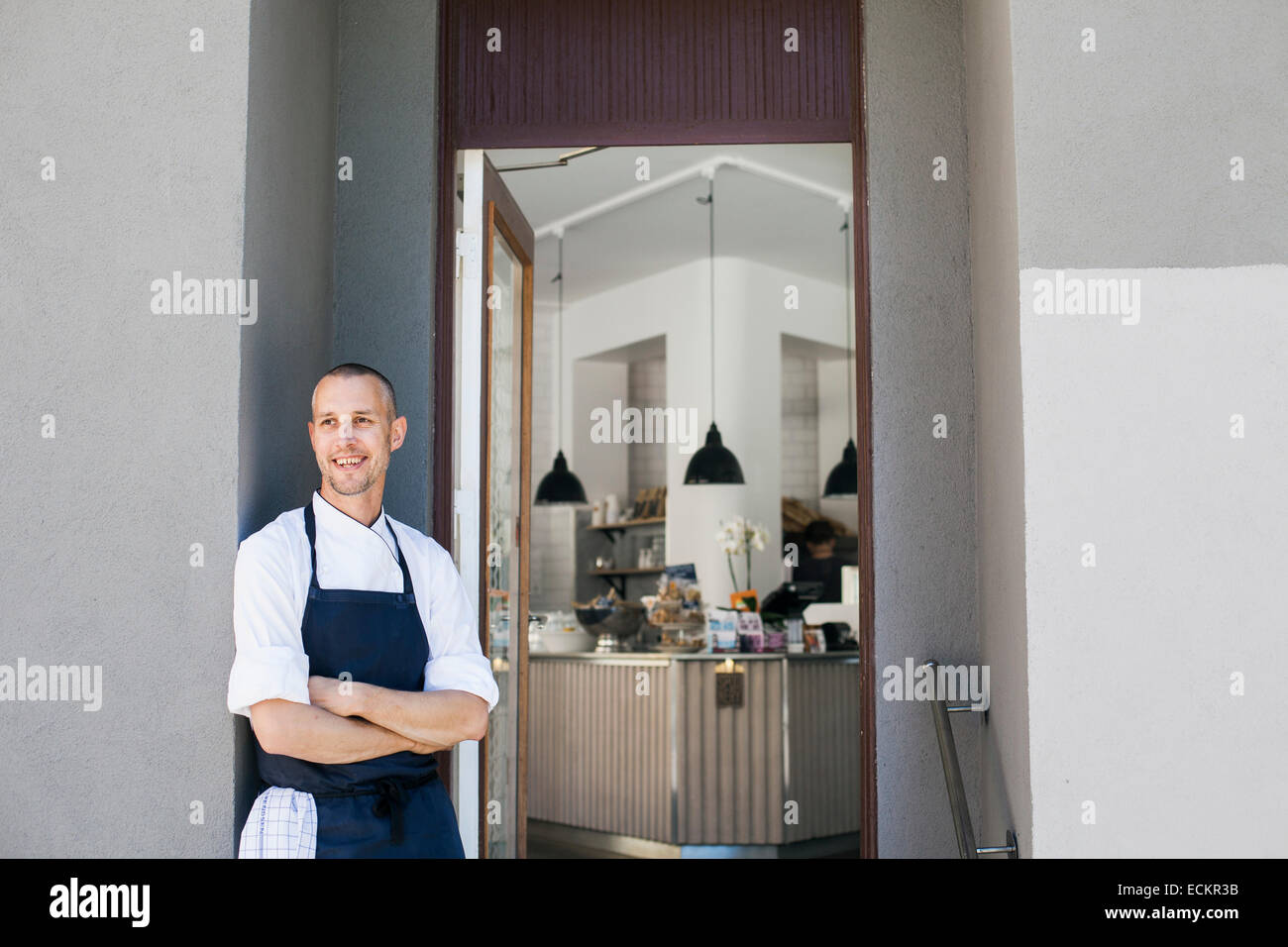 Smiling chef standing arms crossed extérieur cuisine commerciale Photo Stock