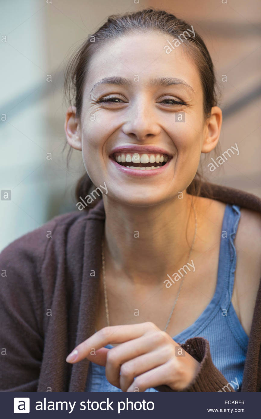 Portrait of young woman laughing outdoors Photo Stock