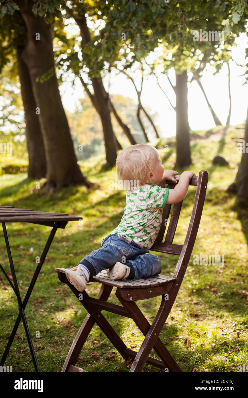 Toute la longueur de baby boy sitting on wooden chair in park Banque D'Images