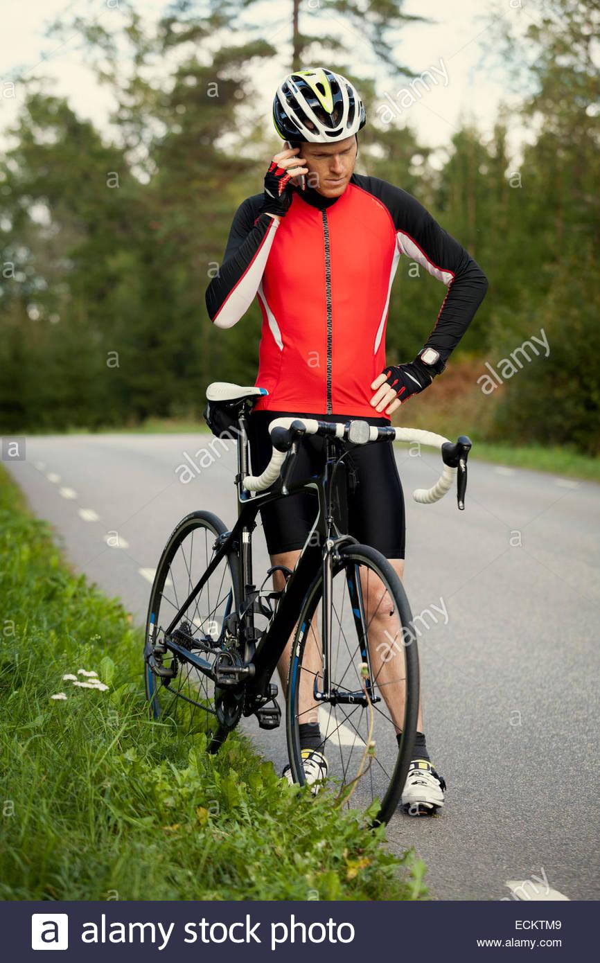 Toute la longueur du téléphone mobile à l'aide d'un cycliste en position debout en vélo Photo Stock