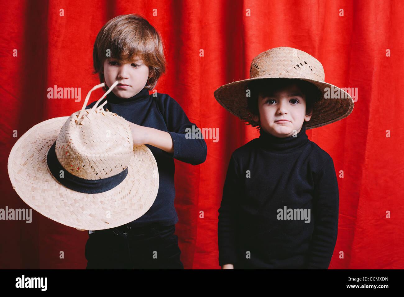 Portrait de deux garçons portant des vêtements noirs et un chapeau de paille Banque D'Images