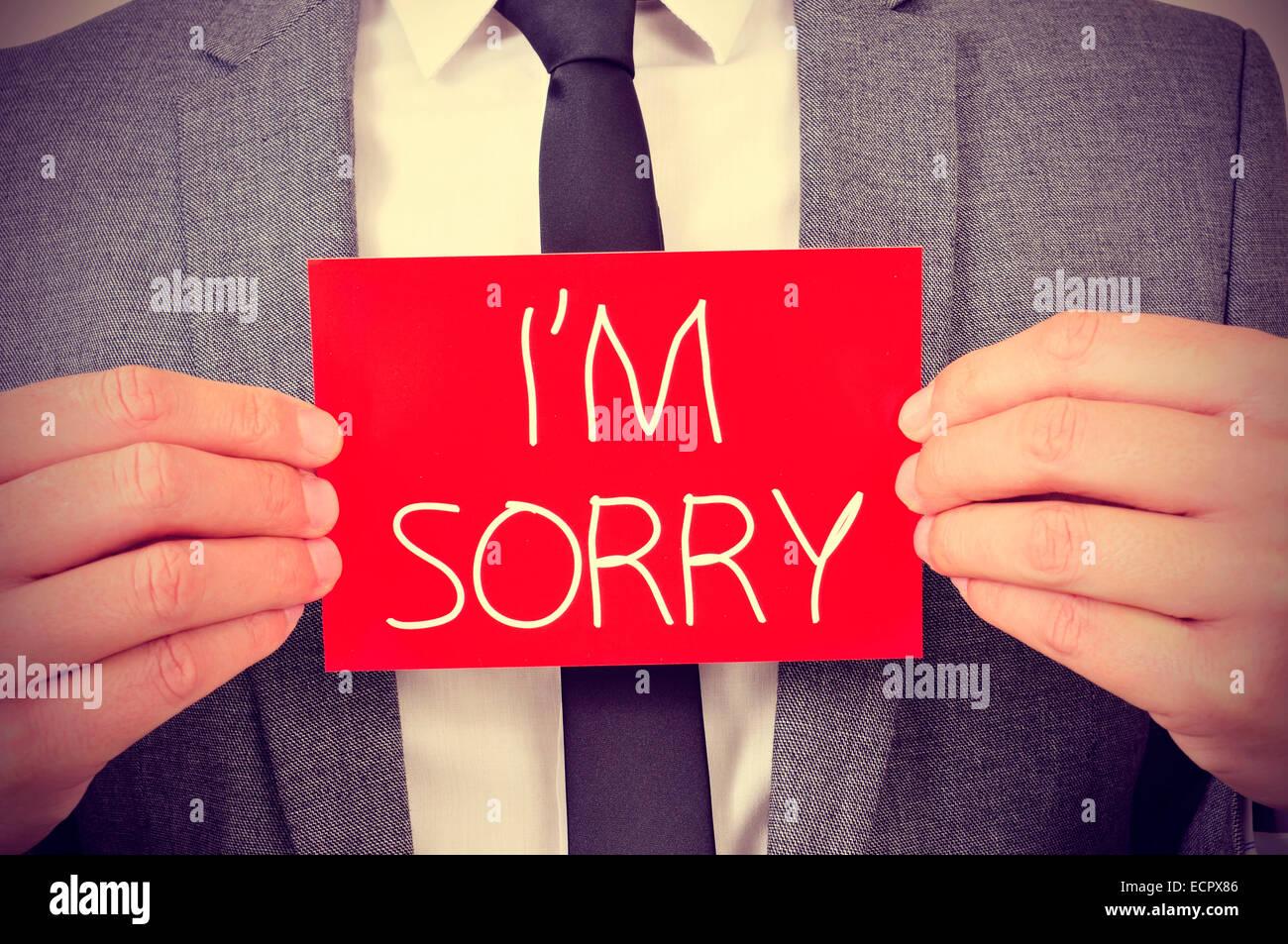 Un jeune homme montrant une pancarte rouge avec le texte Je suis désolé écrit en c Photo Stock
