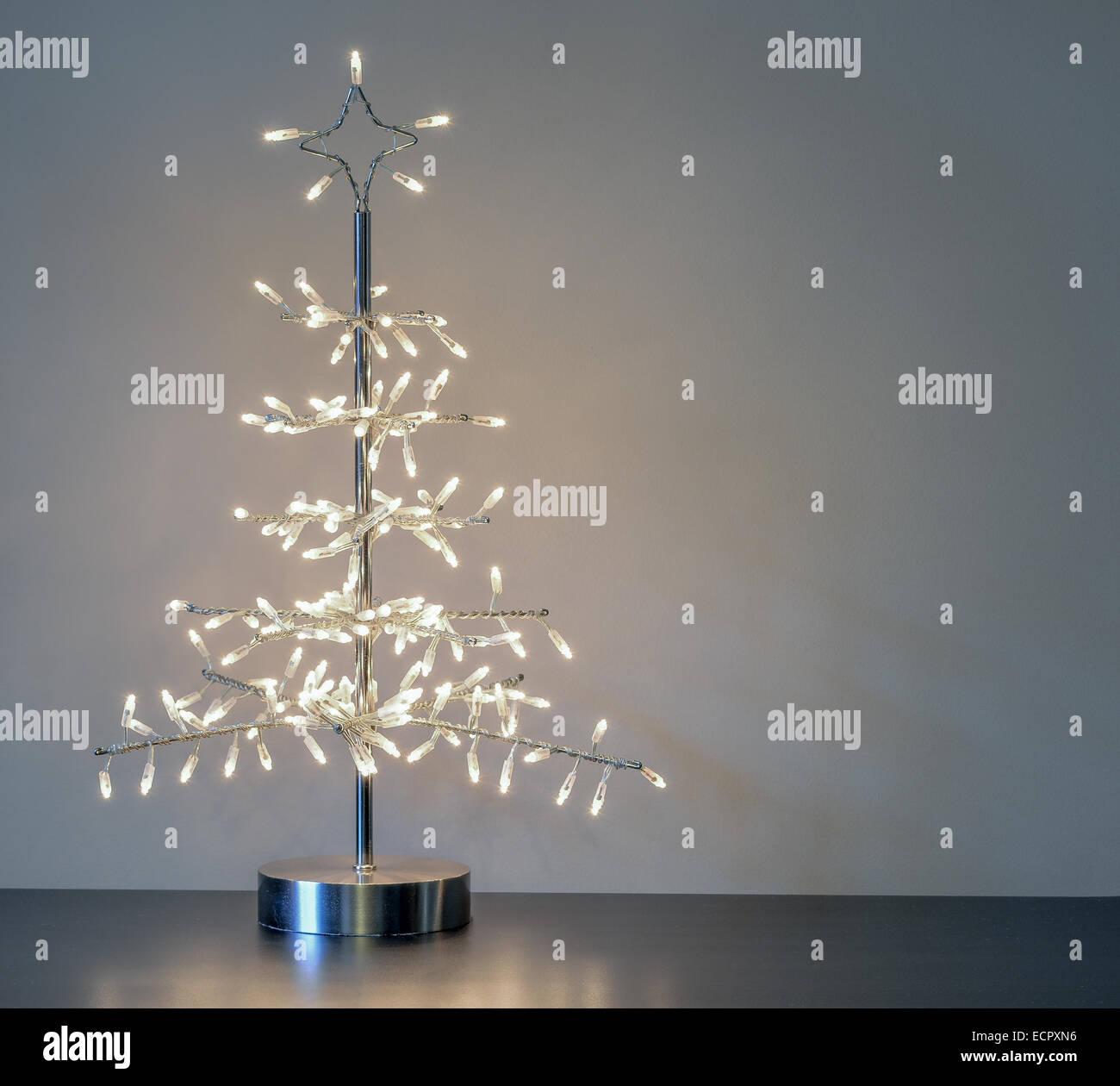 Minimaliste en métal argenté avec ornement d'arbre de Noël feux blanc contre un fond neutre avec Photo Stock