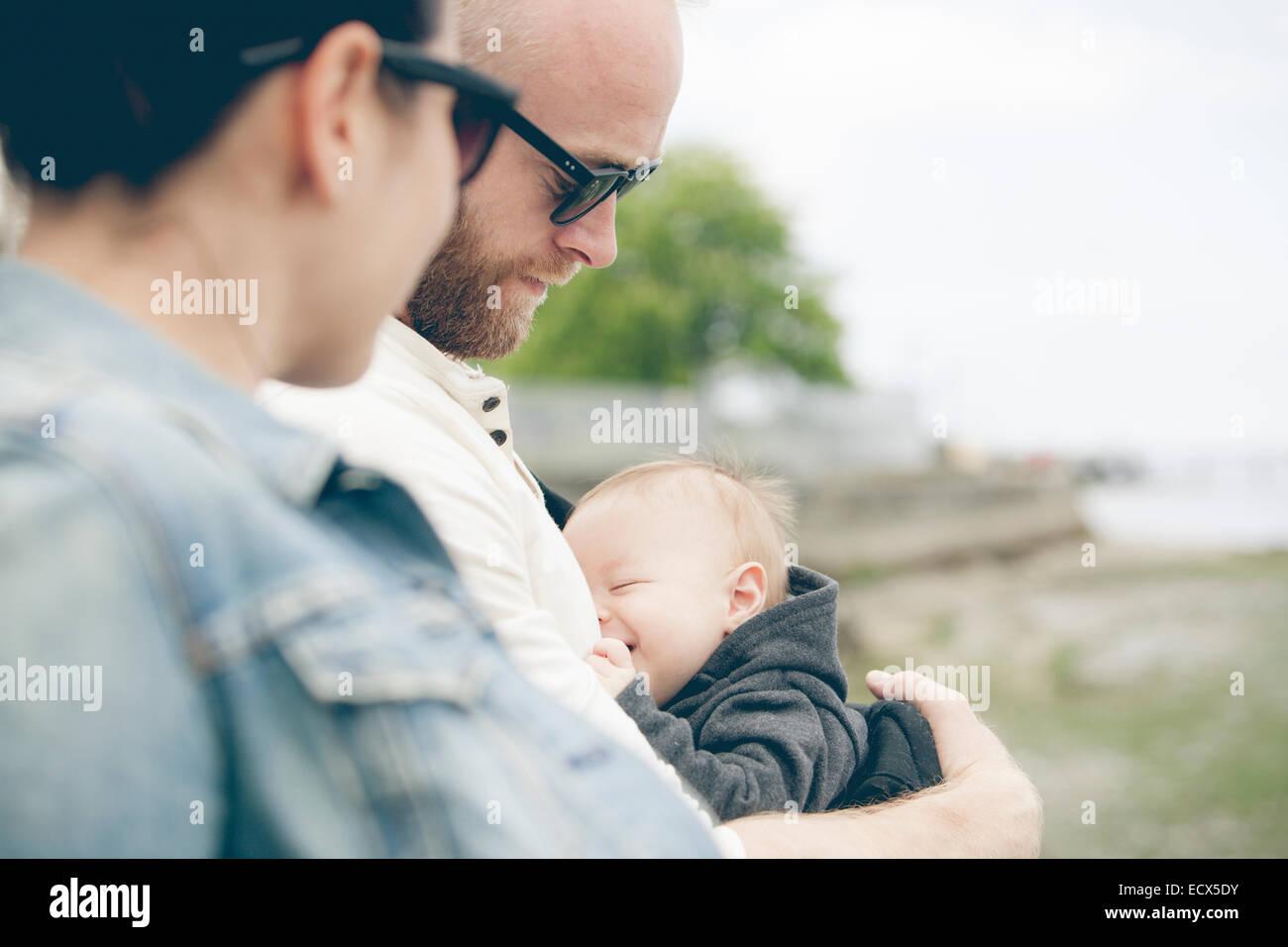 Les parents portant des lunettes maintenant peu baby outdoors Photo Stock