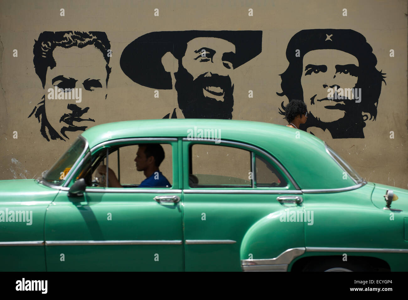 La HAVANE, CUBA - le 13 juin 2011: les lecteurs de voiture américaine classique passé avec panneau pochoir Mella, Cienfuego, et Guevara. Banque D'Images