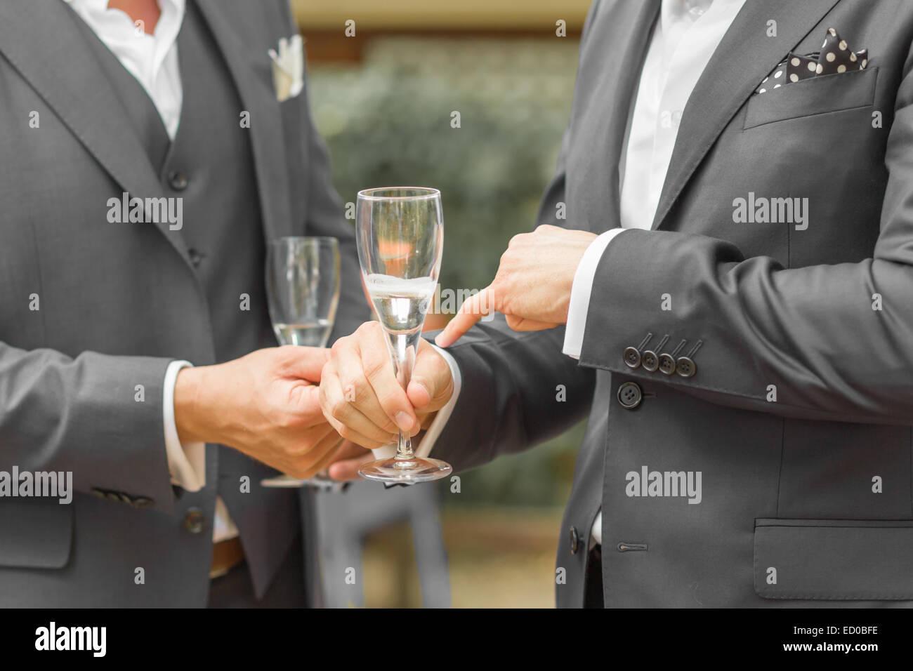 Section intermédiaire de combinaison complète hommes tenant des verres à vin Photo Stock