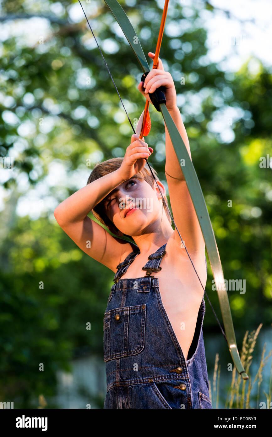 Boy le tournage d'un arc et flèche Photo Stock