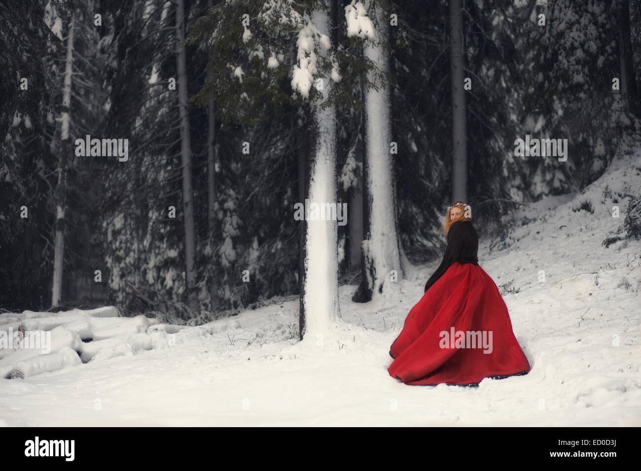 Femme en robe rouge dans la forêt enneigée Banque D'Images