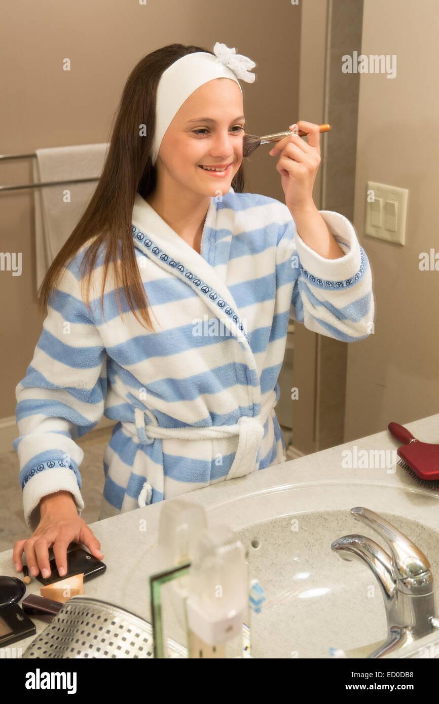 Jeune fille (12-13) à la recherche de miroir tout en appliquant le maquillage Photo Stock