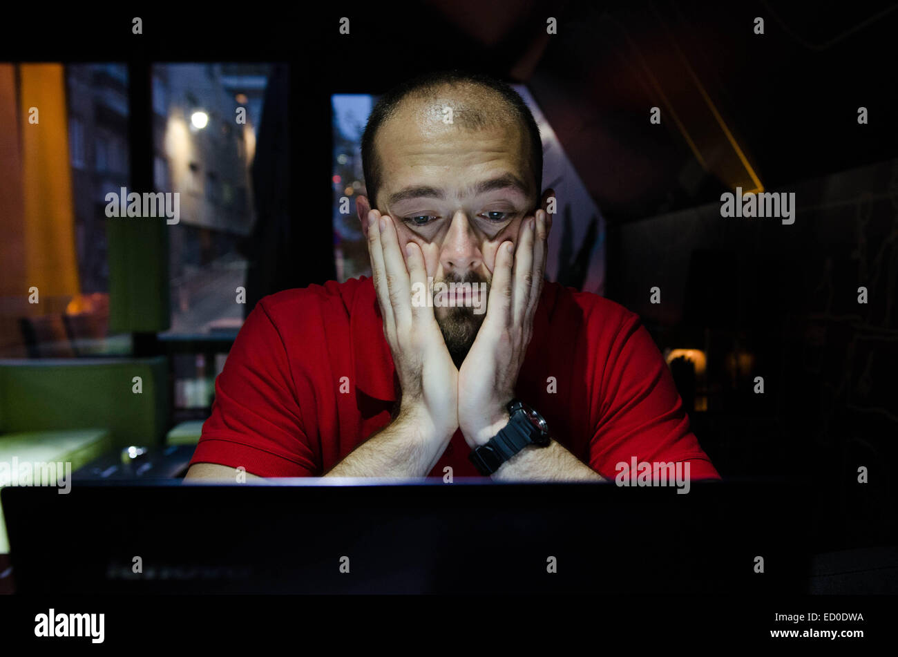 Homme assis et regardant at laptop Photo Stock