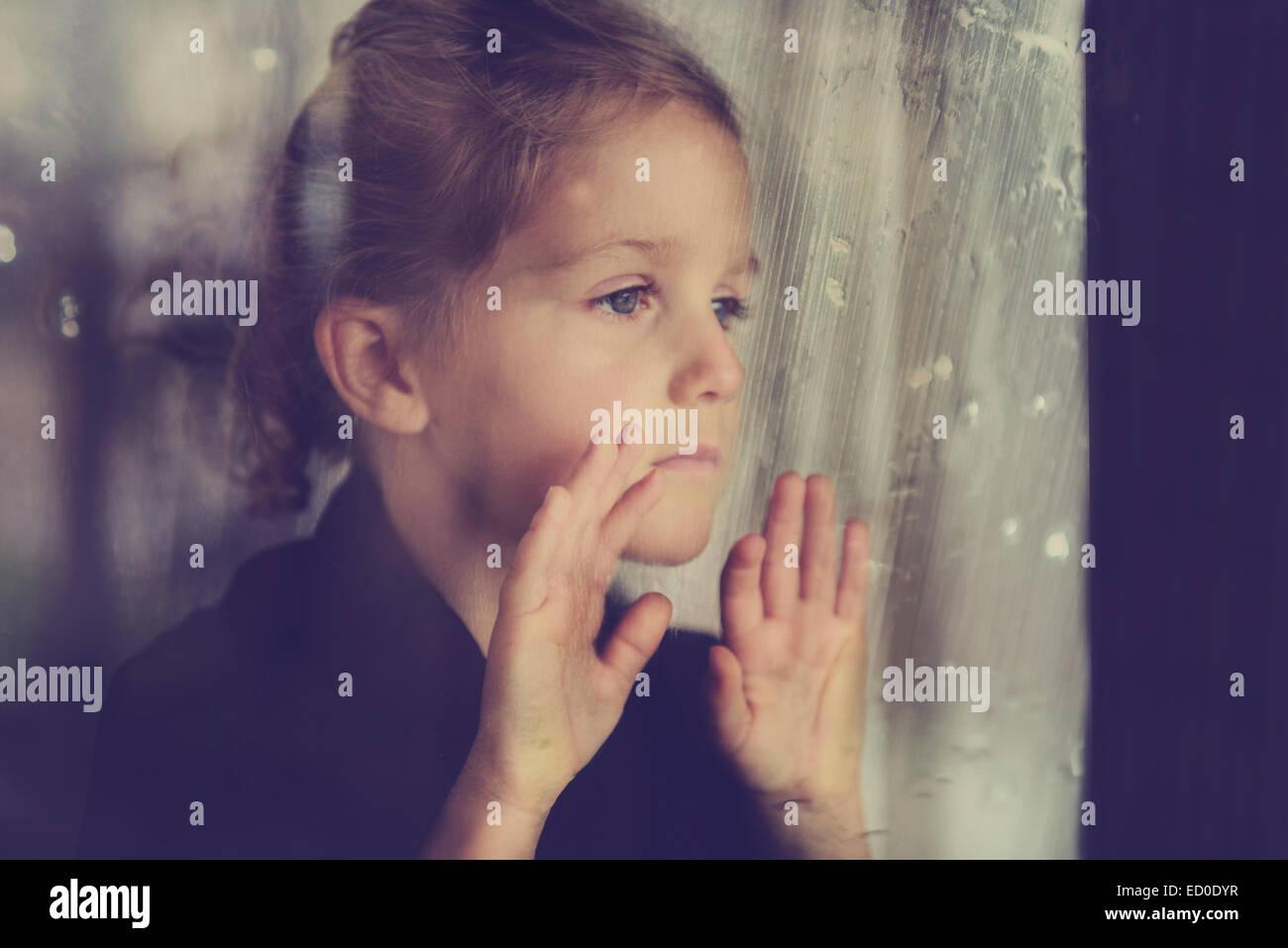 Girl (4-5) grâce à la fenêtre humide Photo Stock