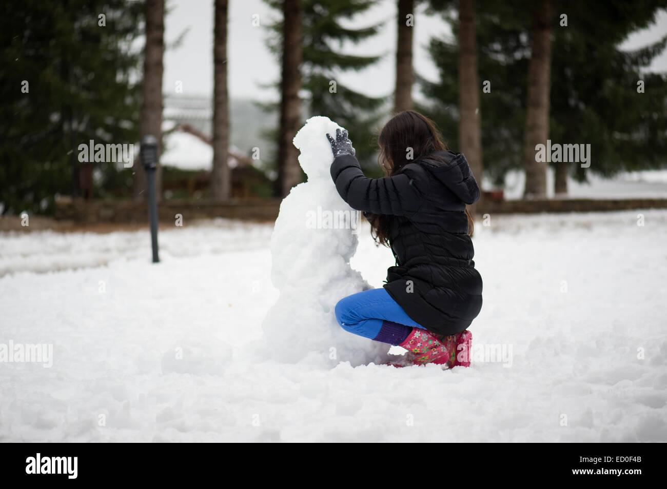 Girl making a snowman Photo Stock
