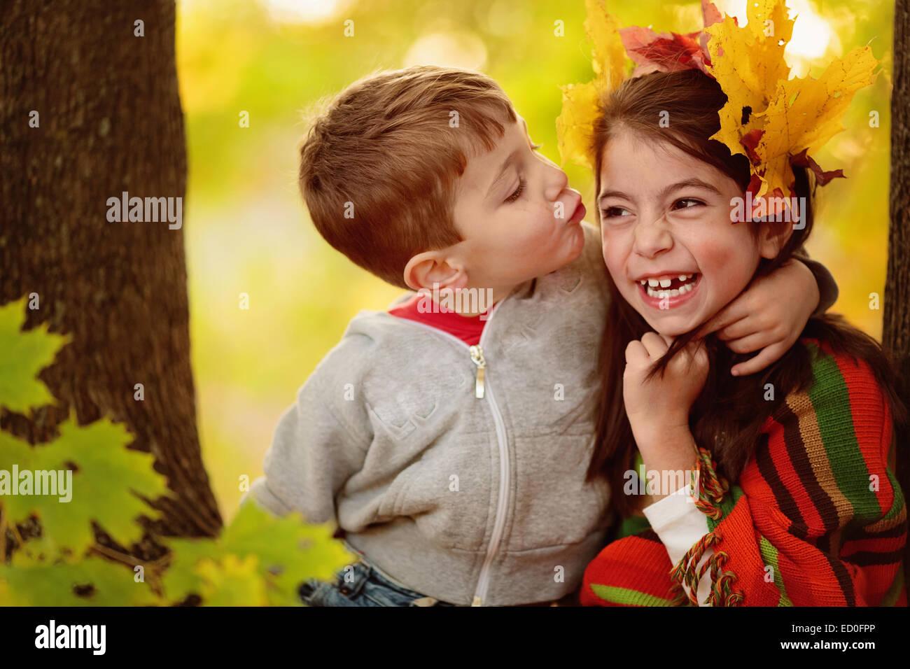Boy hugging une fille, en essayant de l'embrasser Photo Stock