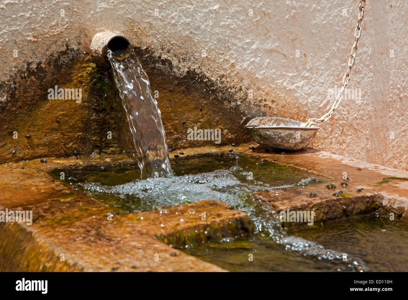 De l'eau frais de montagne bien verser dans la vieille fontaine avec bassin en pierre d'offrir l'eau Photo Stock