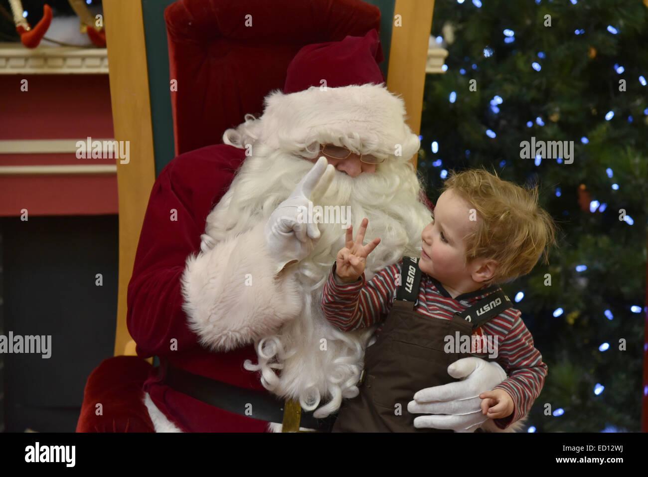 Un petit garçon (2 ans 1/2) assis sur les genoux du Père Noël montrant trois doigts pour dire (à Photo Stock