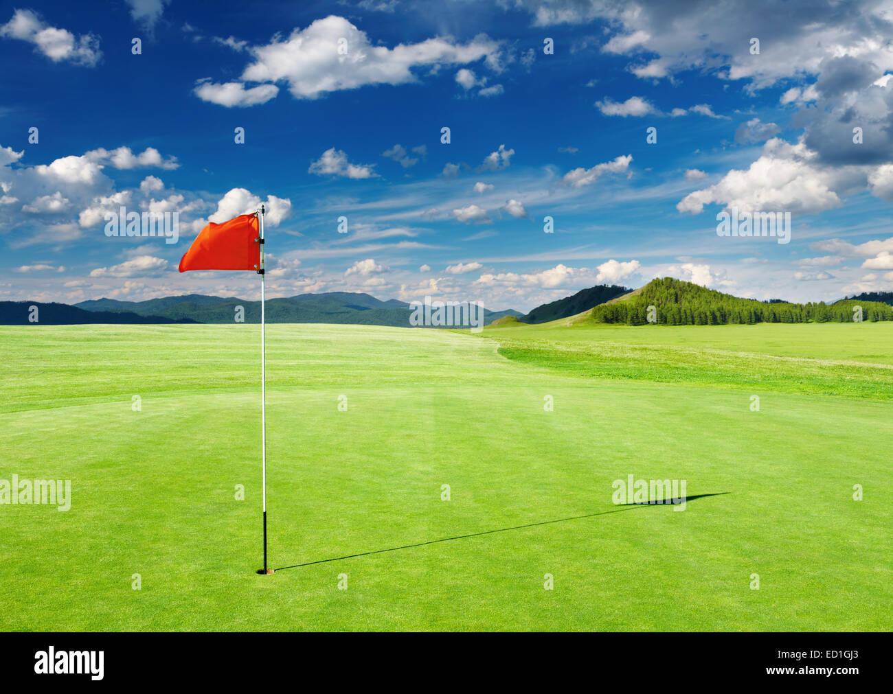 Terrain de Golf avec drapeau rouge dans le trou Photo Stock