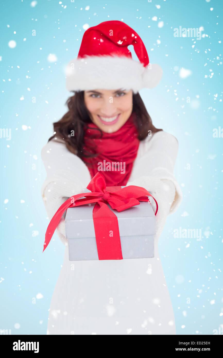 Image composite de brunette de fête à santa hat giving gift Banque D'Images