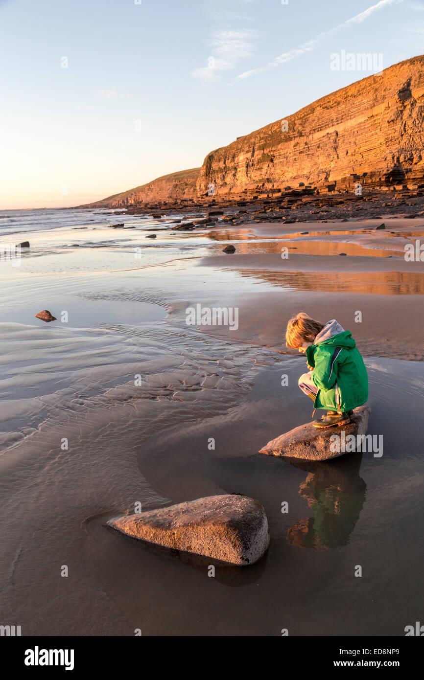 Boy on beach à rock en piscine, Southerndown, Dunraven, Glamorgan, Pays de Galles, Royaume-Uni Photo Stock