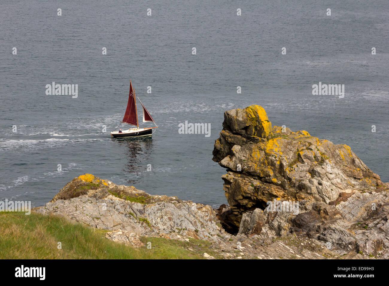 Bateau à voile avec un voile rouge, sur une mer calme, l'Arrondissement Chaises Rock Station de Sauvetage Padstow Cornwall, UK. Banque D'Images
