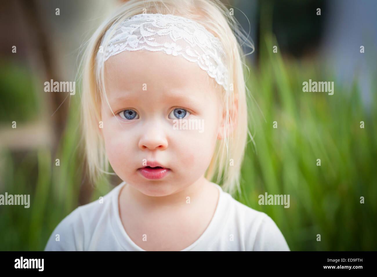Adorable petite fille aux yeux bleus Portrait à l'extérieur. Photo Stock