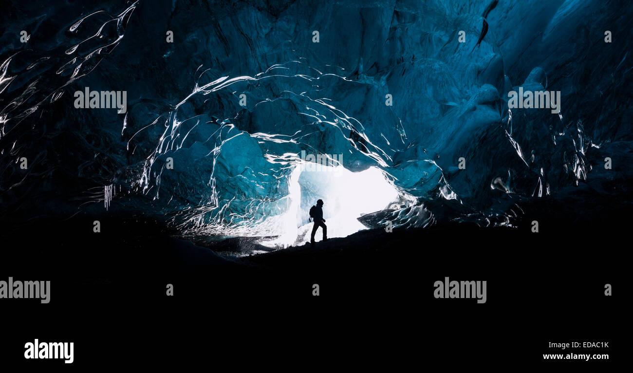 L'homme d'explorer une grotte glaciaire en Islande Photo Stock
