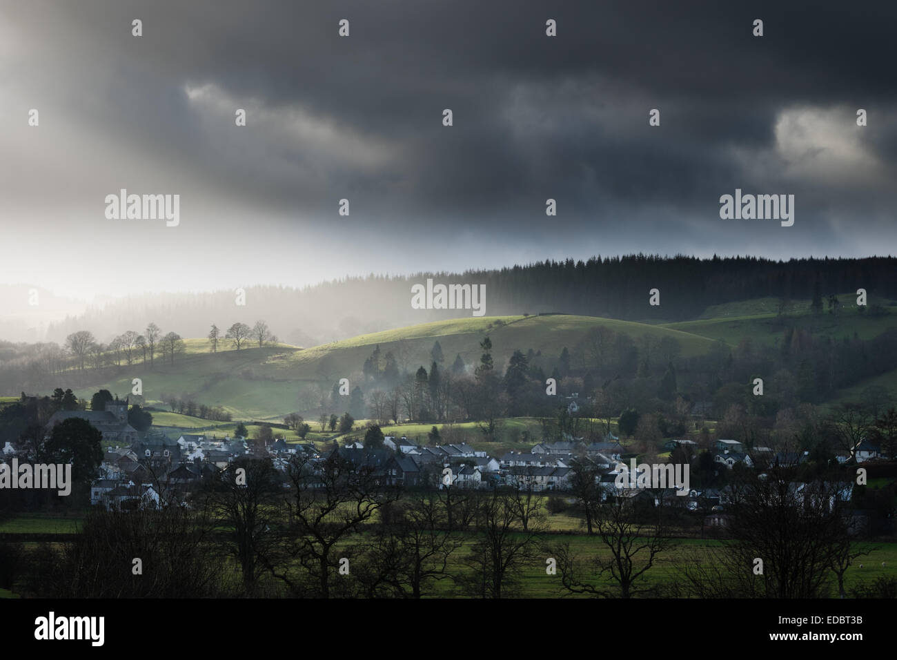 Soleil d'hiver par des nuages sombres pour illuminer le Lake District village de Hawkshead Photo Stock