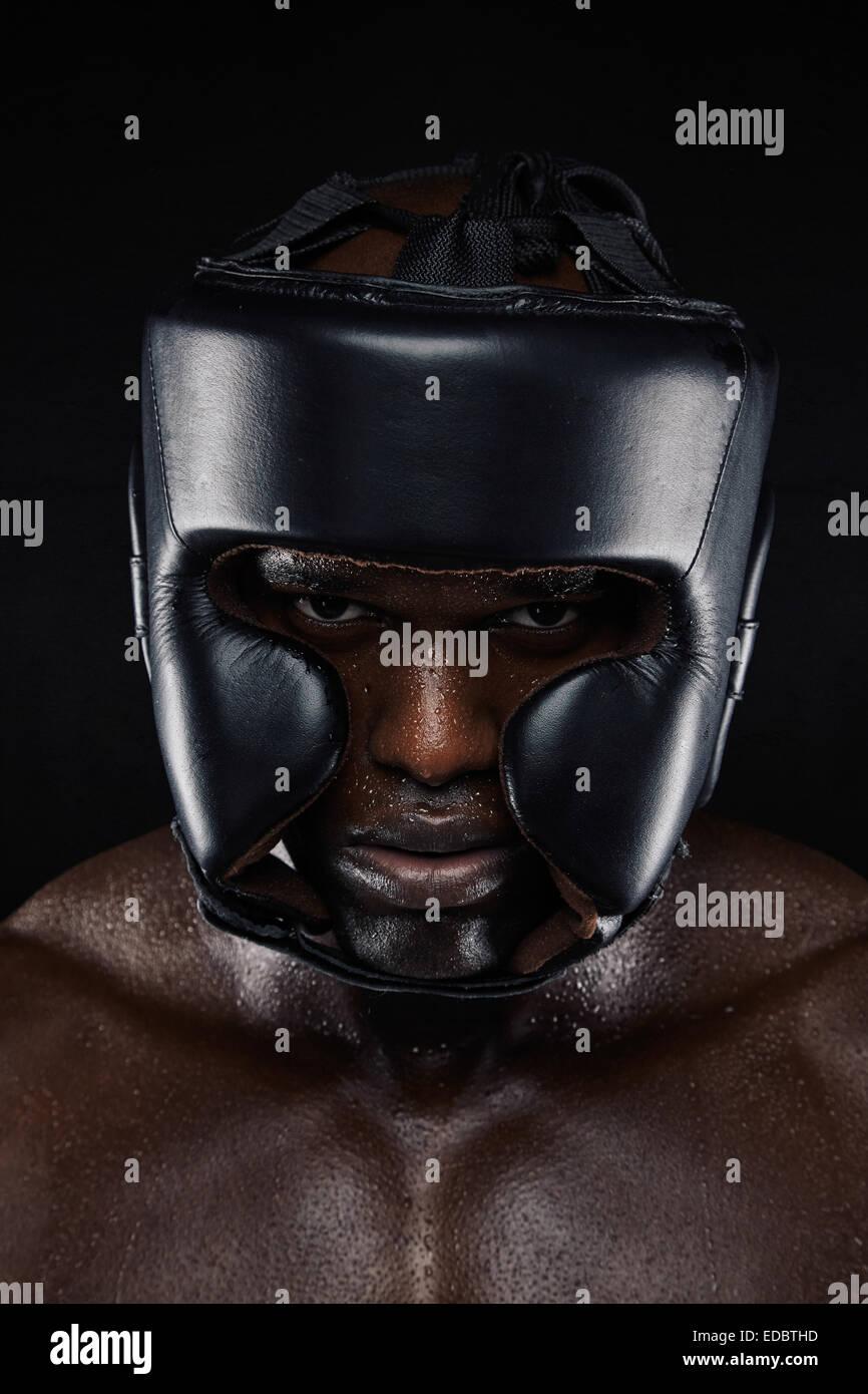 Close-up portrait of strong African man wearing head protector sur fond noir. Tough male boxer en boxe casque. Photo Stock