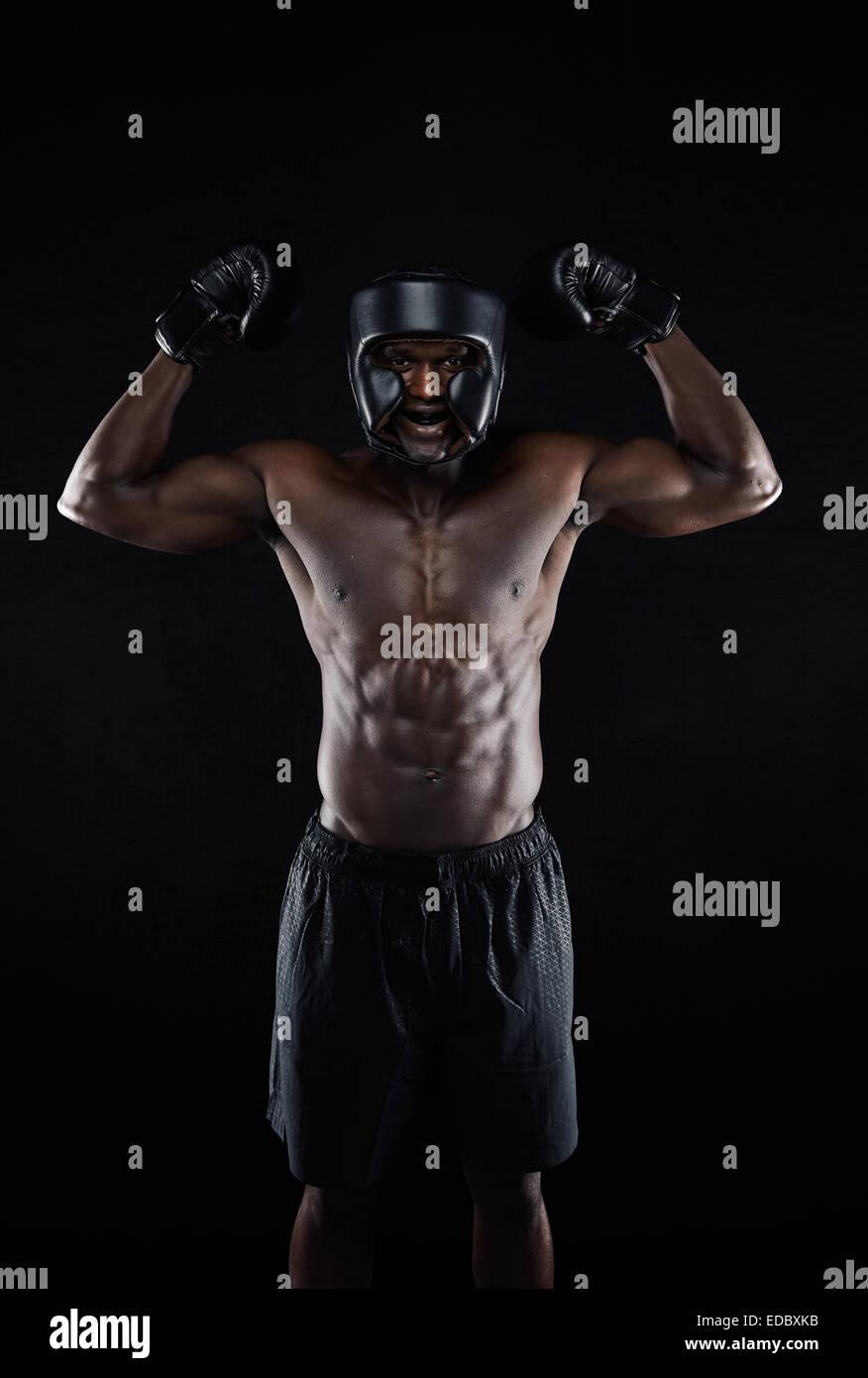 Portrait of happy young African boxing gagnant sur fond noir. Muscular male boxer de célébrer sa victoire Photo Stock