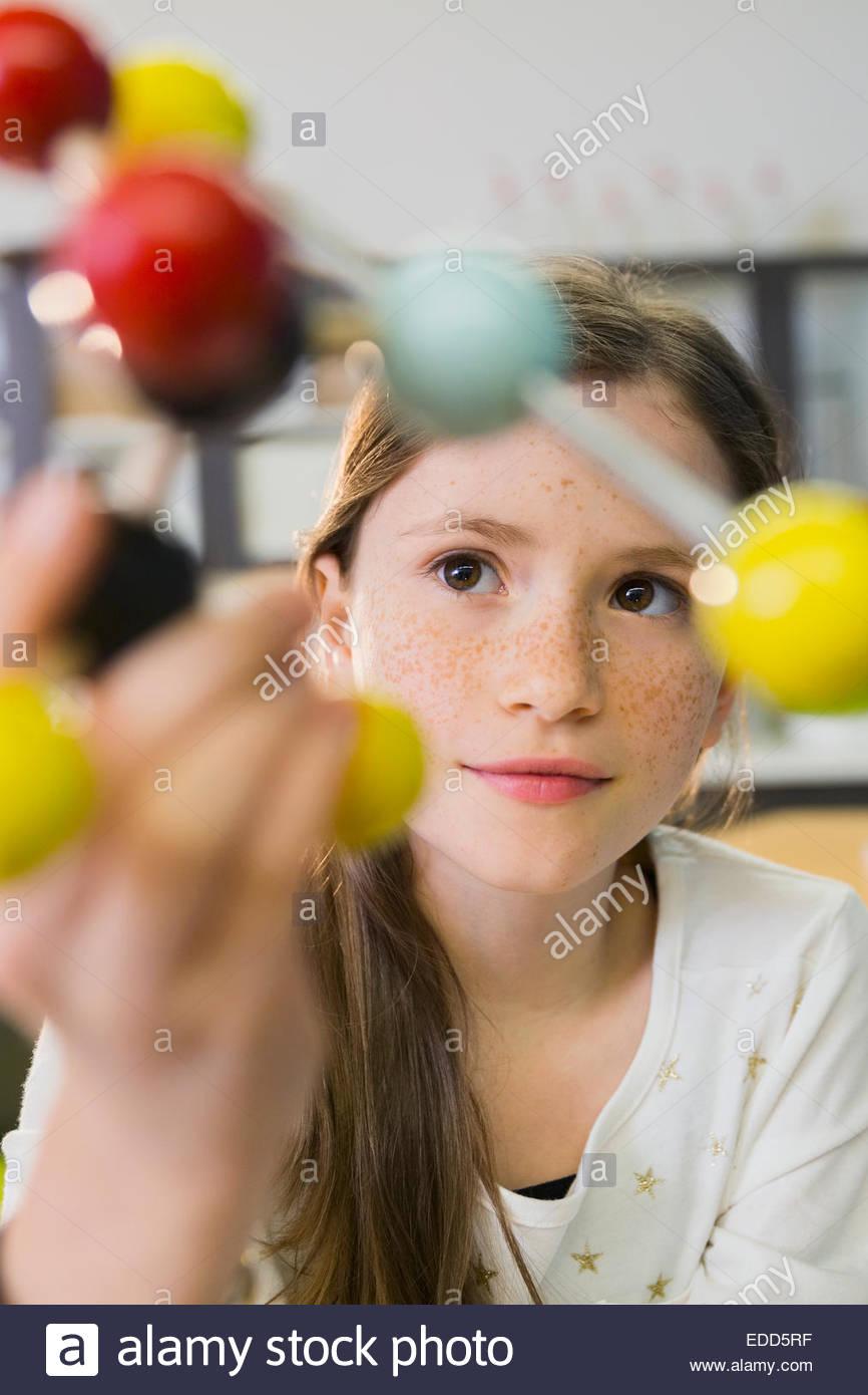 Élève d'école élémentaire l'examen de molécule modèle Photo Stock