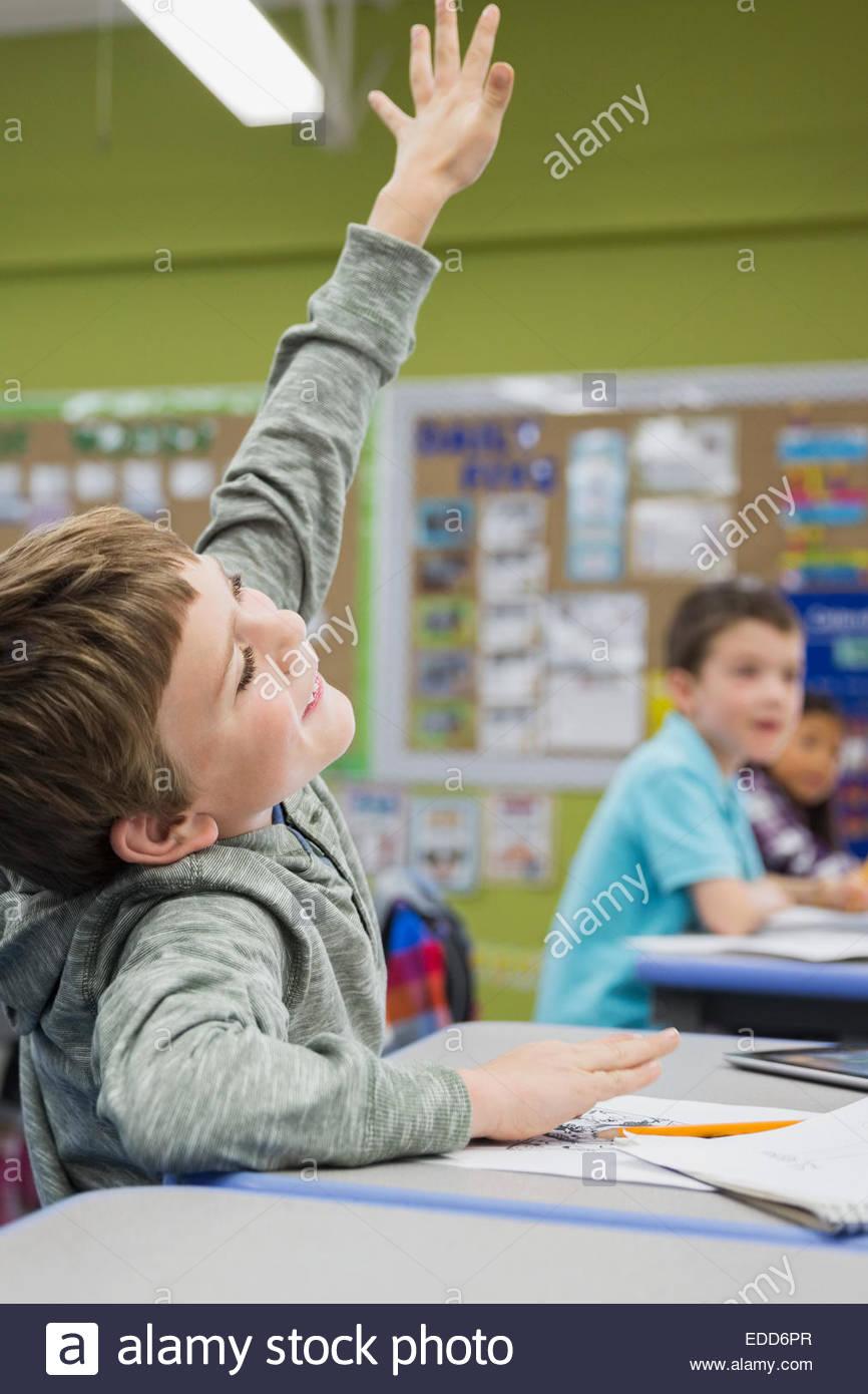 Élève d'école élémentaire enthousiaste avec la main posée en classe Photo Stock