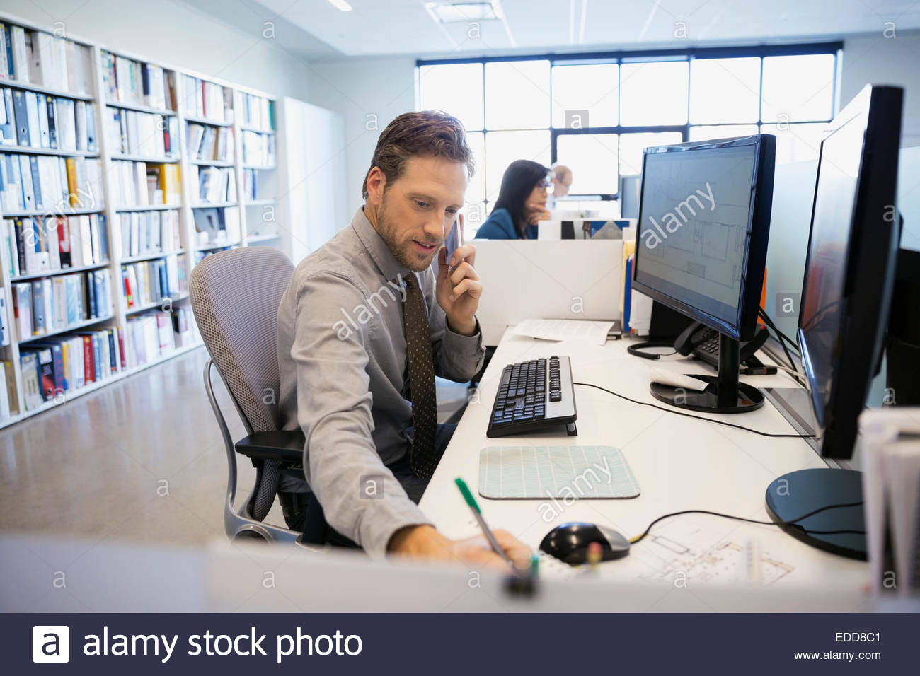 Businessman talking on cell phone at office desk Photo Stock