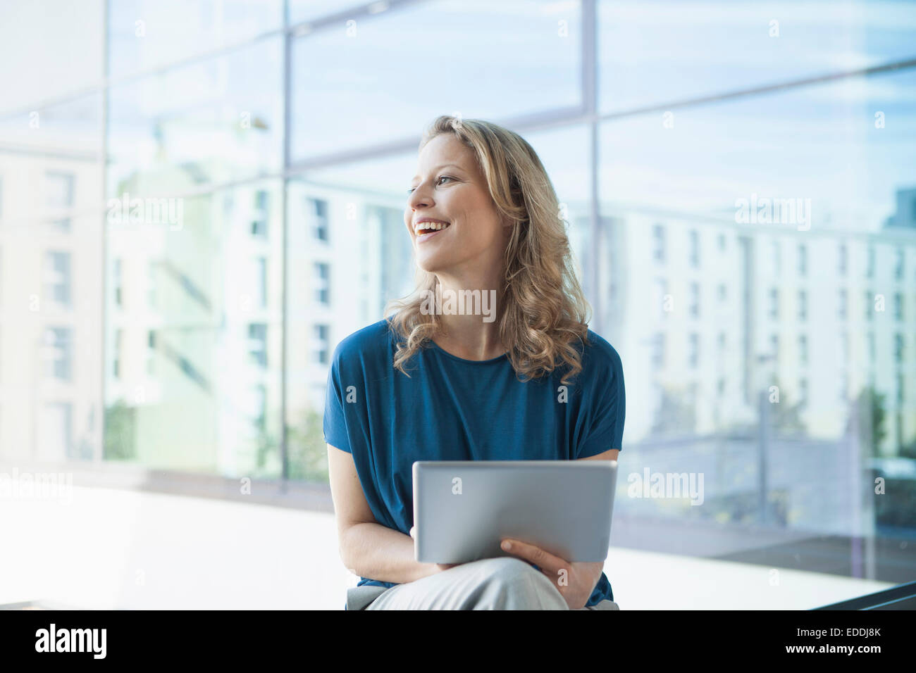 Smiling mature woman with digital tablet assis dans son appartement Photo Stock