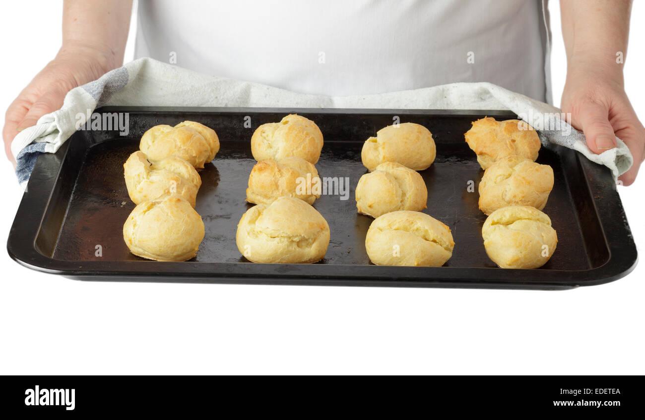 Mains tenant le bac de profiteroles de pâte à choux Photo Stock