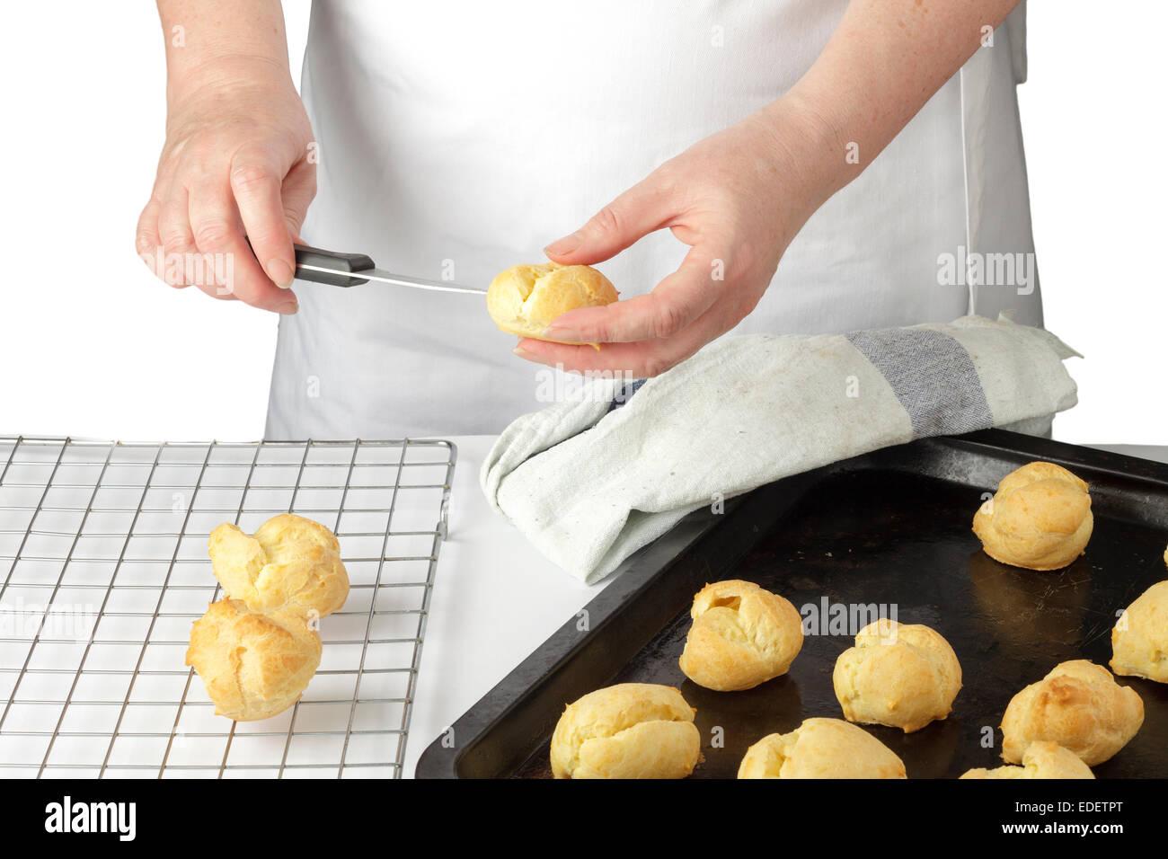 Mains perçant un trou dans une boulangerie juste profiterole Photo Stock