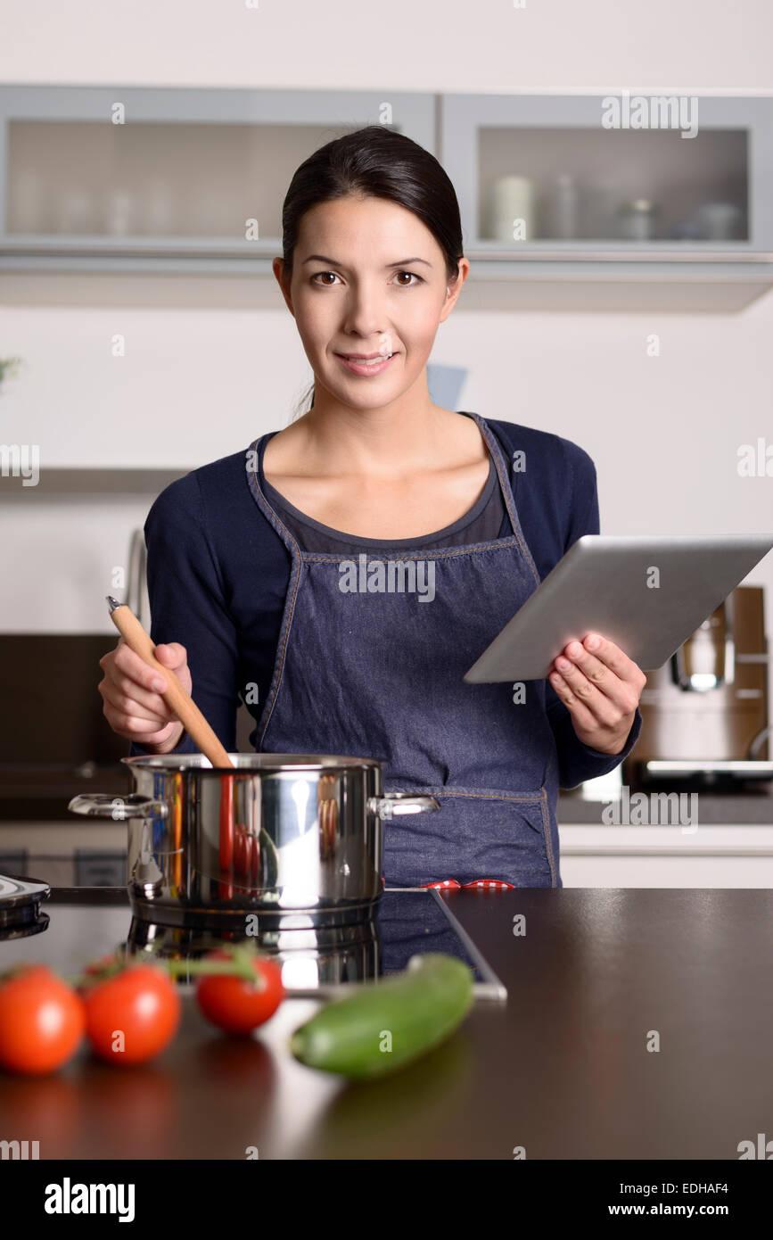 Jeune Femme regardant une recette sur sa tablette comme elle se tient dans la cuisine devant une casserole sur la Photo Stock