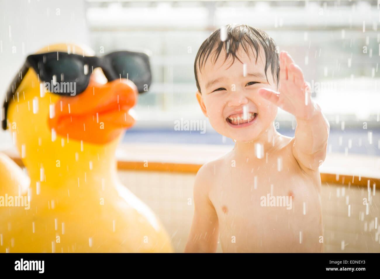 Mixed Race Boy s'amuser au parc aquatique avec grand canard en caoutchouc à l'arrière-plan. Photo Stock