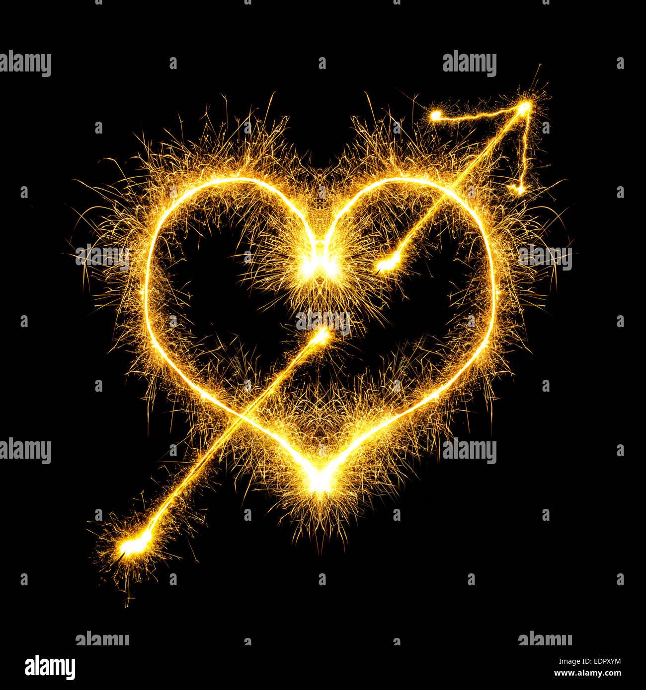 Coeur transpercé étincelles sur fond noir Banque D'Images