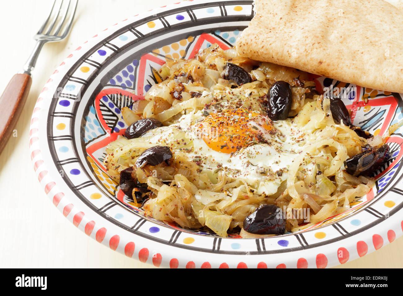 Plat marocain des oignons, ail, piments, olives noires, oeuf et za'atar Photo Stock