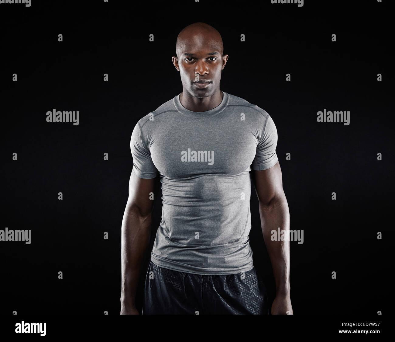 Portrait de jeune homme fit construire musculaire avec l'article sur fond noir. L'afro-américain modèle Photo Stock