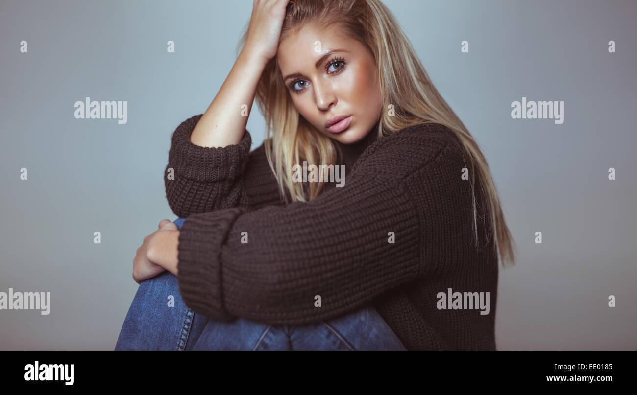Portrait de belle blonde femme chandail en regardant la caméra. Jolie jeune femme en studio. Photo Stock